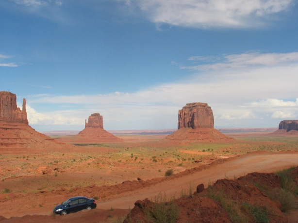 drive down monument valley with East and West Mitten Buttes in background
